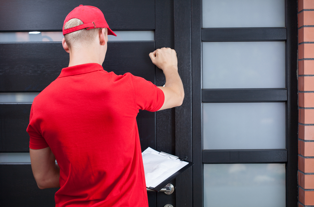 Back view of a delivery man knocking on the clients door